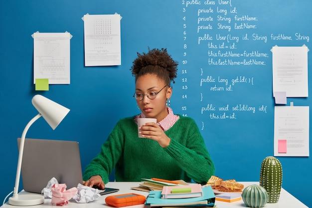 Programadora seria experta trabaja en un proyecto independiente en un espacio de coworking, toma café, usa anteojos redondos y jersey verde. Foto gratis