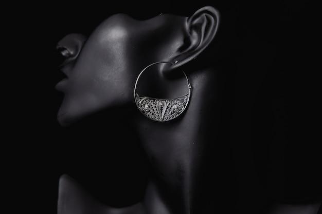 Promoción de joyería fina en los oídos de una mujer Foto gratis