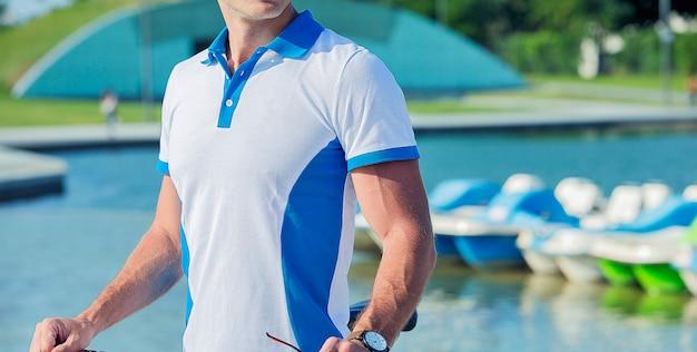 Promoción de modelos masculinos trajes de deportes acuáticos junto a una piscina. Foto gratis