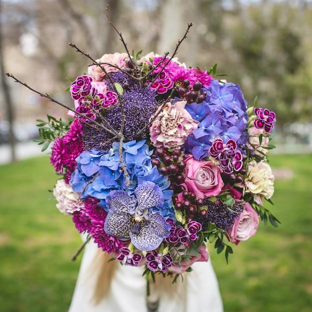 Promoción de un ramo de flores mixtas en un parque Foto gratis