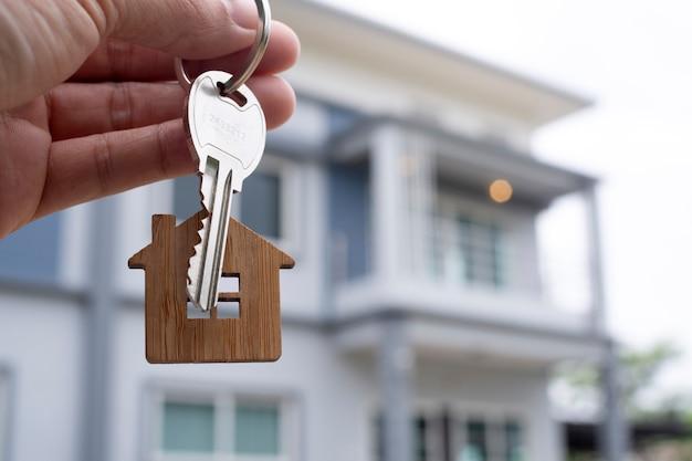 El propietario desbloquea la llave de la casa para un nuevo hogar. agentes inmobiliarios, agentes de ventas. Foto Premium
