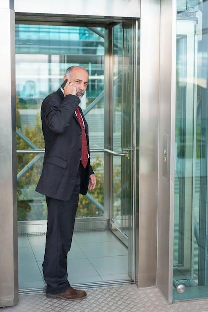 Propietario de negocio maduro serio y centrado hablando por celular Foto gratis