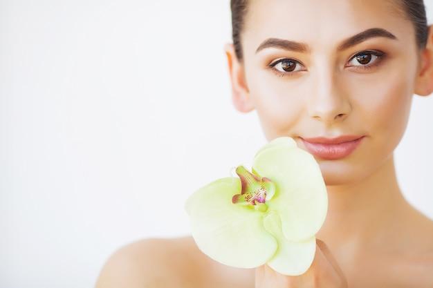 Protección de la piel. belleza de mujer, maquillaje y cuidado de la piel de la cara, flor de orquídea de niña Foto Premium