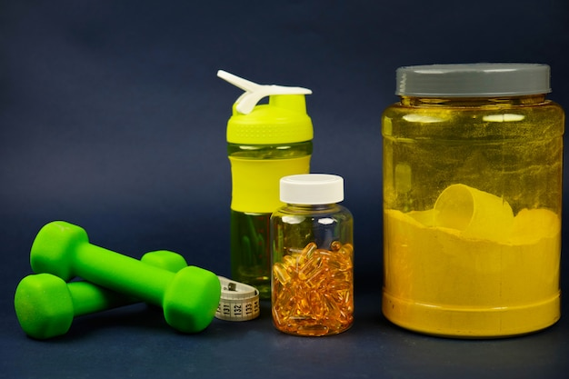 Proteína en un frasco amarillo, agitador de plástico, pesas verdes y un frasco de omega 3 Foto Premium