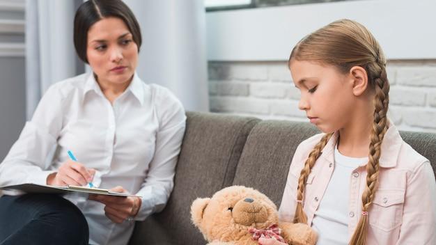 Psicóloga profesional joven que trata de comunicarse con una niña con problemas. Foto gratis