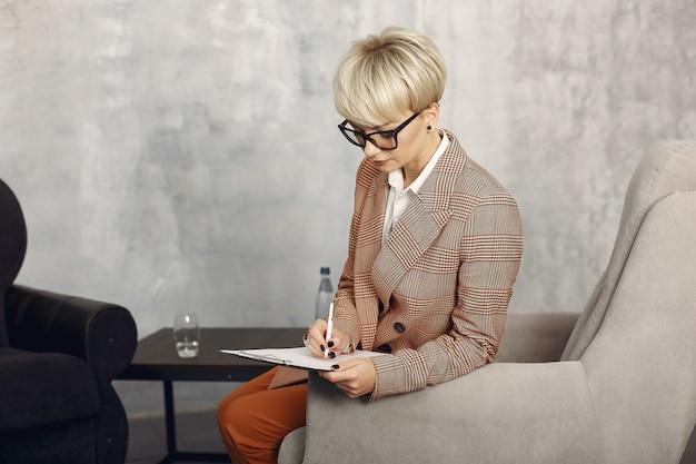 Psicólogo con gafas sentado en una silla en la oficina Foto gratis