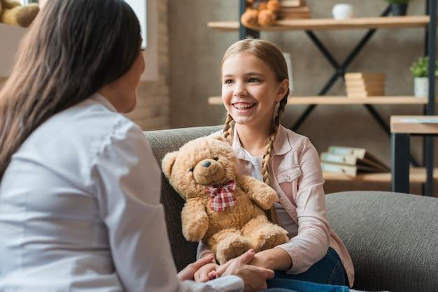 Psicólogo de sexo femenino que habla con la muchacha que sostiene el oso de peluche durante la sesión de terapia Foto Premium