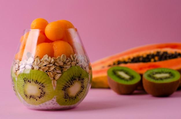 Pudín de chia con kiwi, avena y bolas de papaya en un vaso sobre púrpura Foto Premium