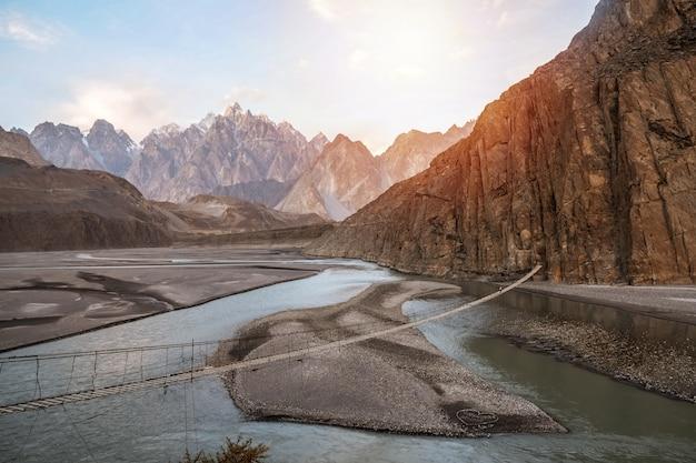 Puente colgante de hussaini sobre el río hunza, rodeado de montañas. Foto Premium