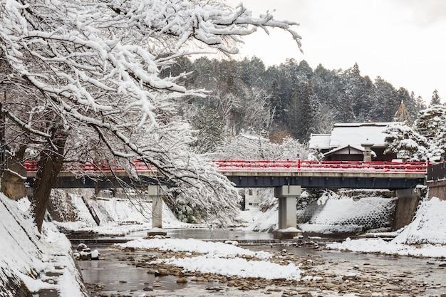 Puente nakabashi con caída de nieve y río miyakawa en temporada de invierno Foto Premium