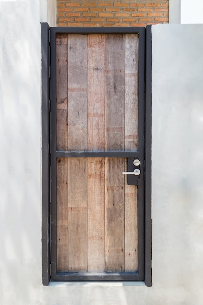 Puerta de madera con marco de hierro en muro de hormig n - Marcos de puertas de madera ...