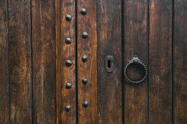Puerta rústica antigua de madera envejecida de la puerta del marrón oscuro con el golpeador del metal. Foto Premium