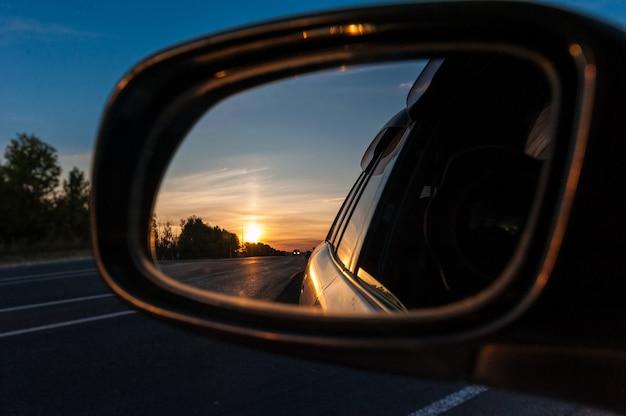 Puesta de sol en el espejo retrovisor de un automóvil Foto Premium