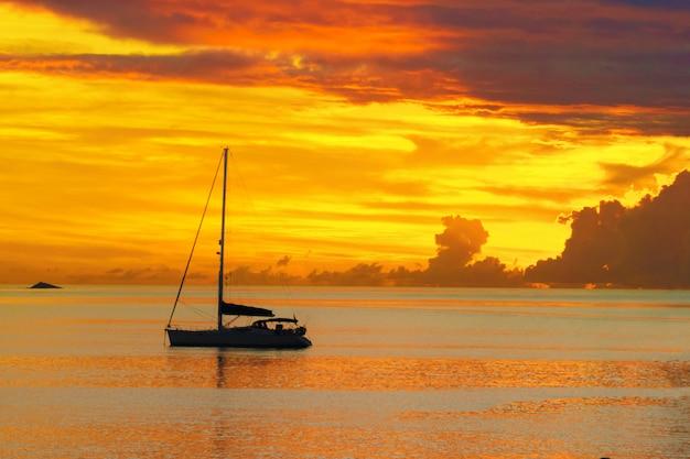 Puesta de sol en el mar y la silueta del yate de vela Foto Premium