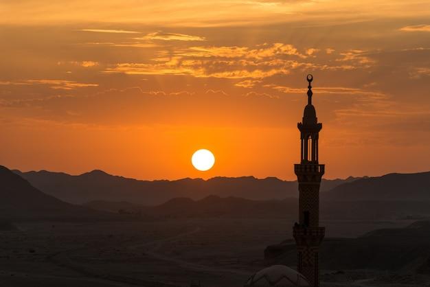 Puesta de sol con mezquita musulmana en primer plano Foto gratis