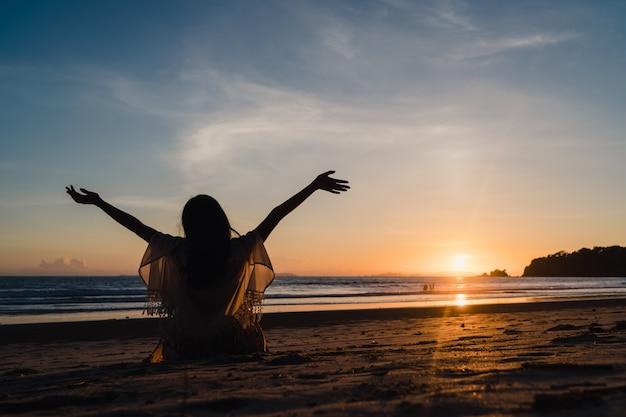 La puesta del sol de observación de la mujer asiática joven cerca de la playa, feliz femenino hermoso relaja disfruta del momento en que puesta del sol por la tarde. Foto gratis