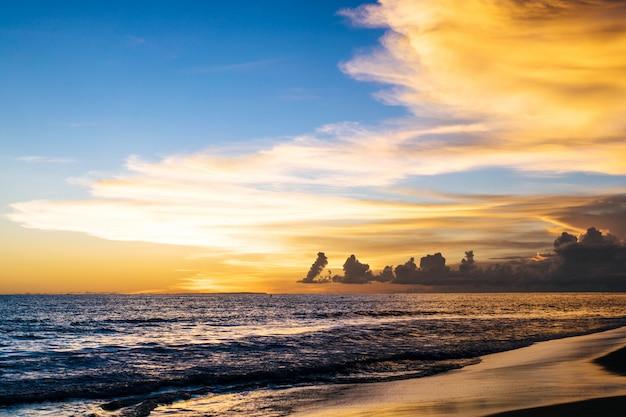 Puesta de sol en el océano. hermoso cielo brillante, reflejo en el agua, las olas. Foto gratis