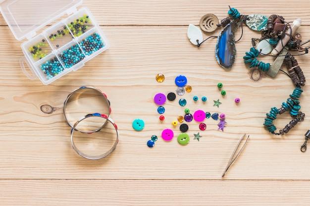 Pulseras y joyas decorativas hechas a mano en la mesa de madera Foto gratis