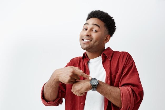 Que hora es. retrato de joven atractivo hombre de piel oscura con peinado afro oscuro en camiseta blanca y camisa roja apuntando a mano reloj con expresión de cara feliz, mostrándole la hora de comer. Foto gratis
