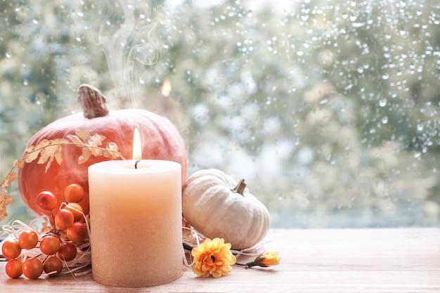 Quema de velas, calabazas y decoraciones de otoño en una ventana Foto Premium