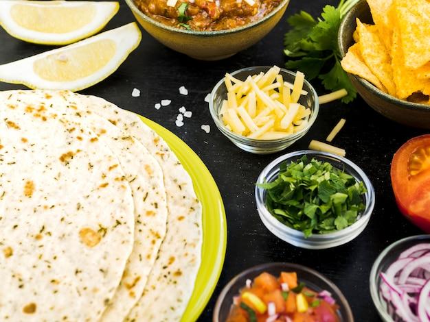 Quesadilla junto a tazas con verduras y papas. Foto gratis