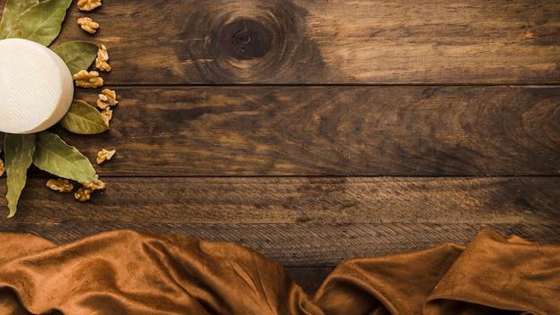 Queso manchego español con hojas secas de laurel y nogal en superficie de madera vieja Foto gratis