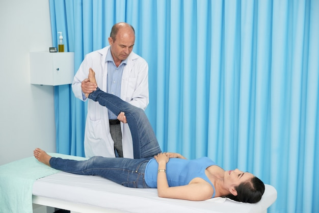 Quiropráctica manipulando la pierna del paciente en la sesión de rehabilitación Foto gratis