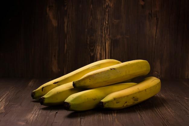 Racimo de plátanos maduros sobre fondo de madera rústico Foto Premium