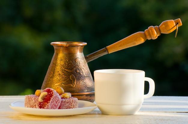 Rakhat lokum, cezve y una taza de café a la luz del sol Foto Premium
