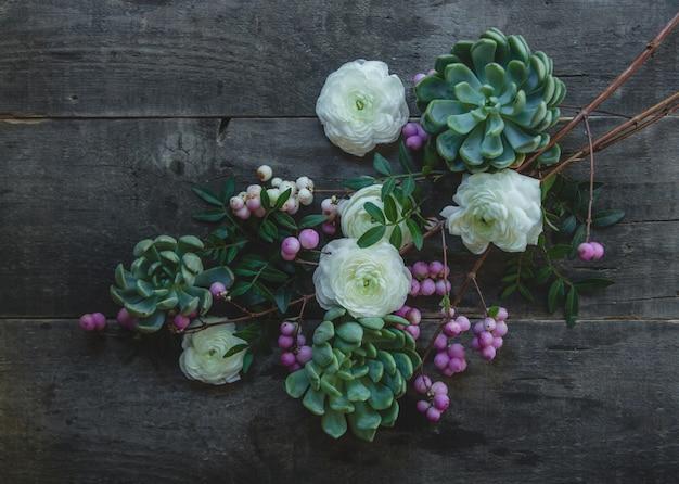 Una rama de flores de flor blanca y púrpura en una mesa de madera. Foto gratis