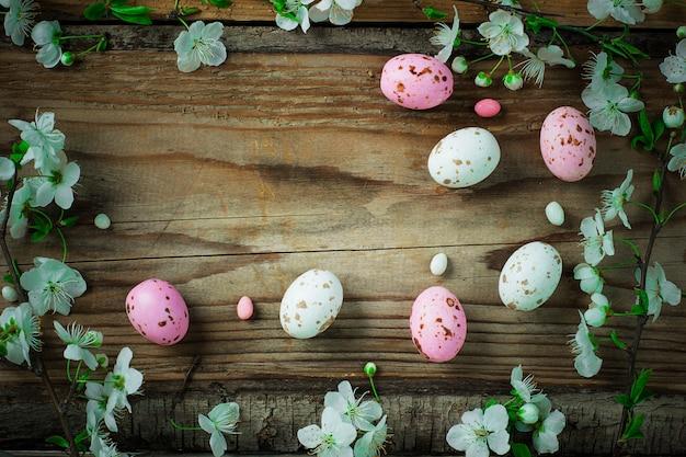 Rama de flores de primavera y coloridos huevos de caramelo rosa para pascua en rústico Foto gratis