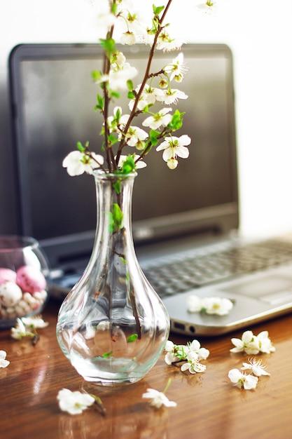 Rama de flores de primavera y coloridos huevos de caramelo rosa para pascua Foto gratis
