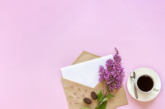 Rama de lila en sobre de artesanía con tarjeta vacía en blanco blanca para texto y taza de café Foto Premium