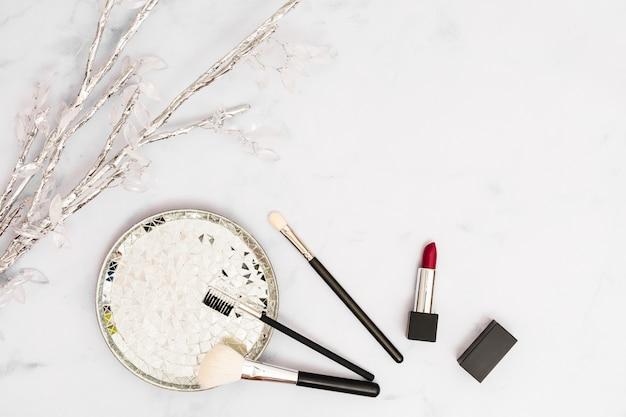 Rama de plata y cristal con placa; pinceles de maquillaje y lápiz labial sobre fondo blanco Foto gratis
