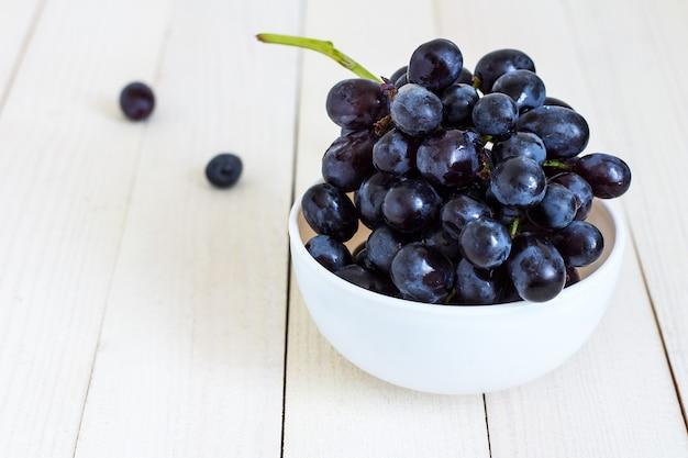 Rama de uva negra en un tazón de madera blanca Foto gratis