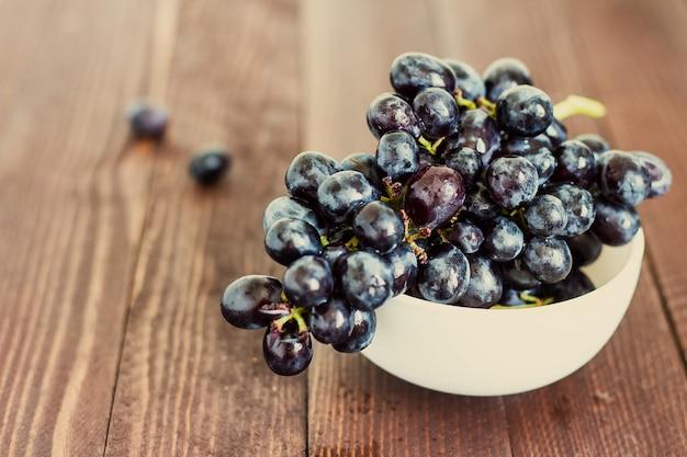 Rama de uva negra en un tazón de madera oscura Foto gratis