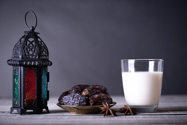 Ramadán concepto de alimentos y bebidas. farol de ramadan con leche, dátiles frutales. Foto Premium