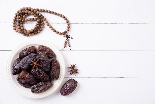 Ramadán concepto de alimentos y bebidas. rosario de madera y frutos en una mesa de madera blanca. Foto Premium