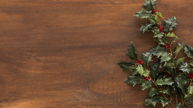 Ramas de acebo verde en mesa marrón Foto gratis