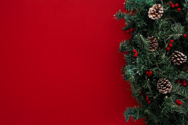 Ramas de los árboles de navidad sobre fondo rojo. Foto gratis