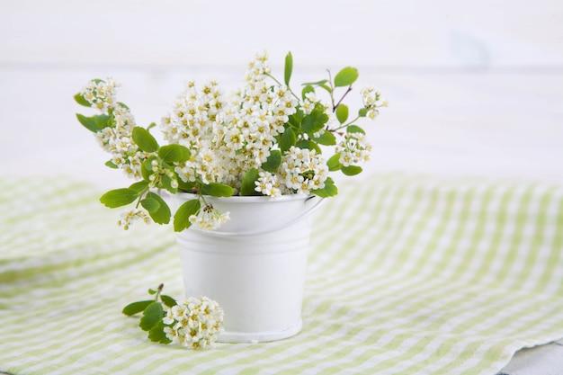 Ramas florecientes en un florero en una textura de madera. estilo japonés wabi sabi. decoración del hogar Foto Premium