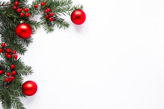 Ramas de pino y decoraciones rojas con espacio de copia Foto gratis