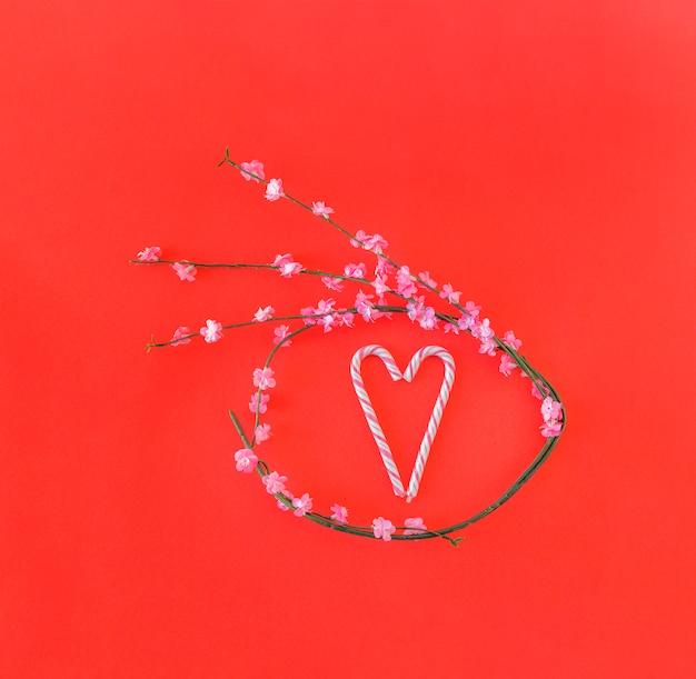 Ramita con flores en forma de círculo y bastones de caramelo en forma de corazón Foto gratis