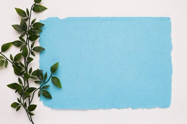 Una ramita verde artificial cerca del papel rasgado azul sobre fondo blanco. Foto gratis