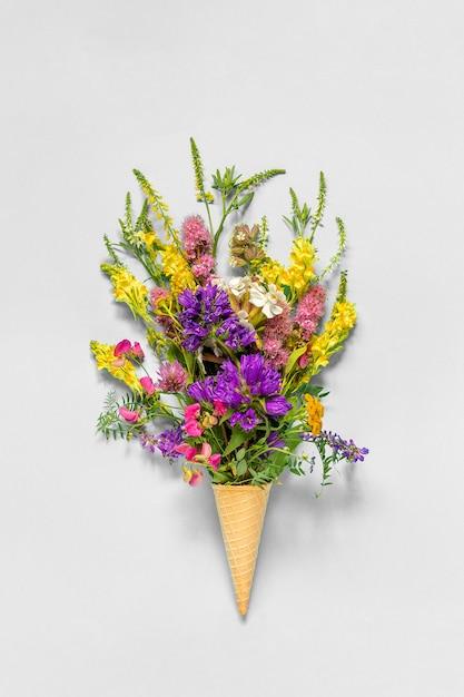Ramo de campo flores de colores en cono de helado de galleta sobre fondo de papel gris vista plana vista superior mock up concepto día de la mujer o día de la madre Foto Premium