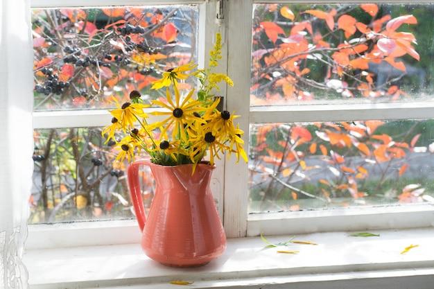 Ramo de flores amarillas en florero sobre alféizar Foto Premium