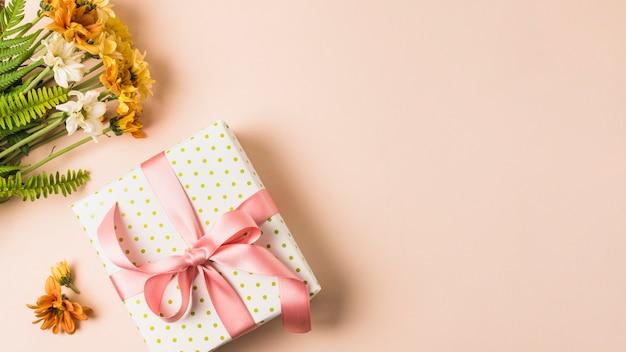 Ramo de flores blancas y amarillas cerca de la caja actual envuelta sobre superficie de melocotón Foto gratis