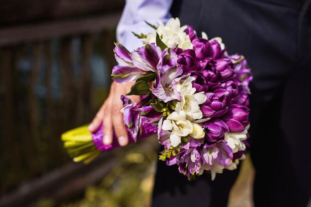 Ramo de flores blancas y moradas en la mano novio ramo de flores en la mano de un hombre, un hombre de negocios con un ramo de flores Foto Premium