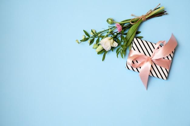 Ramo de flores, caja de regalo, cinta sobre fondo azul con espacio de copia Foto Premium