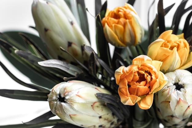 Un ramo de flores exóticas de protea real y tulipanes brillantes. plantas tropicales en composición florística. Foto gratis